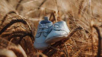 babies shoes on top of wheat