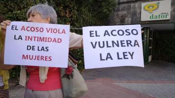 """mujer con dos carteles: """"el acoso vulnera la intimidad de las mujeres"""" y """"el acoso vulnera la ley"""""""