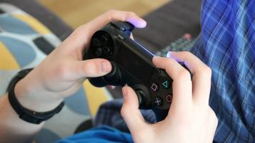 manos joven jugando consola